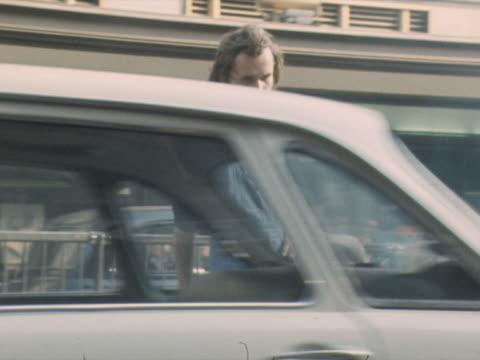 vidéos et rushes de a man crosses the road wearing denim dungarees - salopette