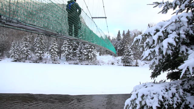 Man Crossing a Suspension Bridge in Winter