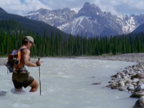 vidéos et rushes de man crossing mountain stream - un seul homme d'âge moyen