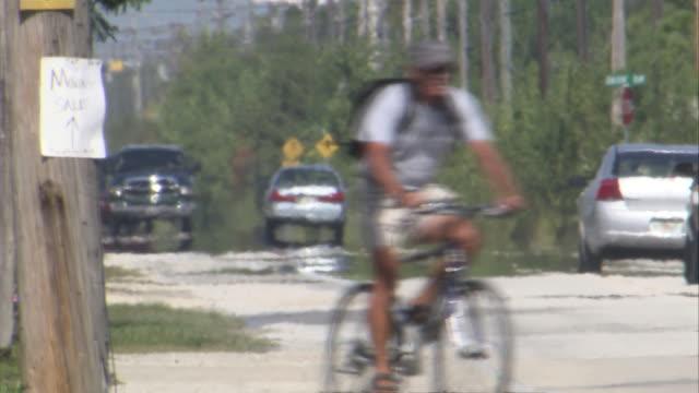 ms man crossing road on bycical   / florida keys, florida, usa - heat haze stock videos & royalty-free footage