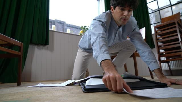 man crouching on floor going through paperwork - crouching stock videos & royalty-free footage