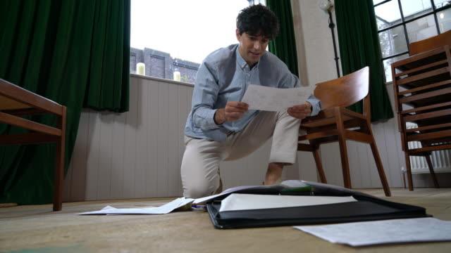 man crouching on floor going through paperwork - arranging stock videos & royalty-free footage
