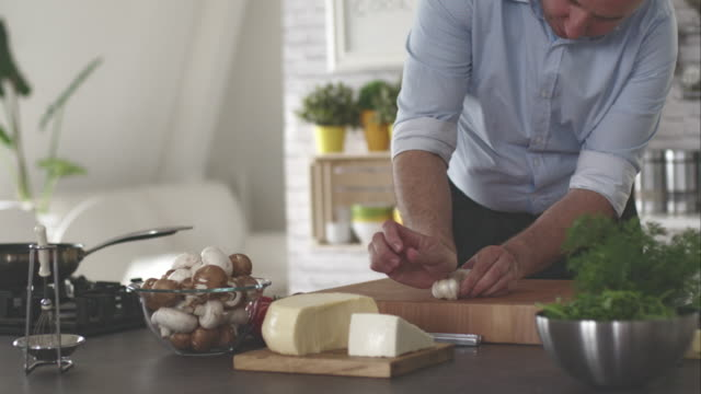 Man crushing garlic on cutting board in the kitchen