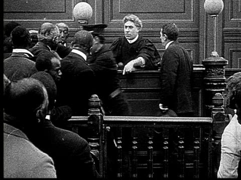 1916 b&w ms man crying as police take him from courtroom/ spectators leaving  - 1916年点の映像素材/bロール