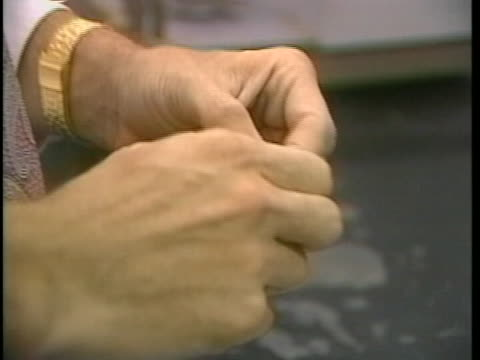 stockvideo's en b-roll-footage met man cuts a chunk of crack-cocaine into smaller rocks with a razor, and then puts them into small baggies. - crime or recreational drug or prison or legal trial