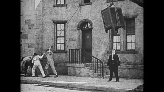 1921 man (buster keaton) cuts a rope being used to hoist a large piece of furniture into an apartment with hopes of being crushed underneath it, but it misses him and breaks into pieces, upsetting the workmen - hoisting stock videos & royalty-free footage