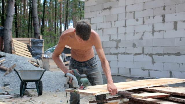 vídeos y material grabado en eventos de stock de hombre corta un tablón de madera con una sierra circular. - madera material de construcción