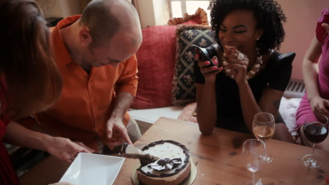 man cutting and serving birthday cake at dinner party - birthday cake stock videos and b-roll footage