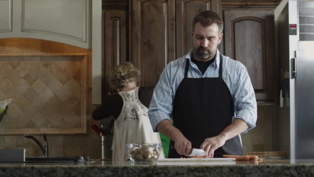 ms tu man cutting carrot in kitchen / orem, utah, usa - orem bildbanksvideor och videomaterial från bakom kulisserna