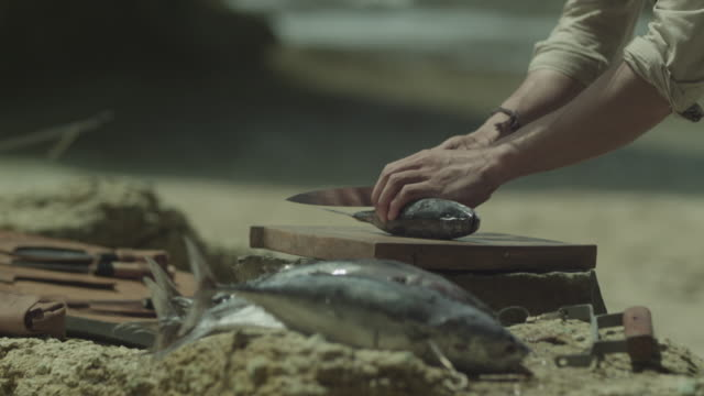 Man cutting fish by the shore.