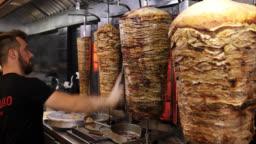 Man cutting gyro in fast food restaurant