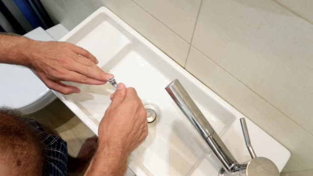 man cutting his hand's nails in a bathroom in slow motion - fingernail stock videos & royalty-free footage
