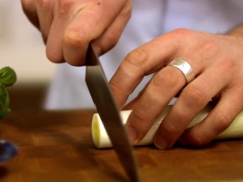 vidéos et rushes de man cutting leek sweden. - un seul homme d'âge moyen