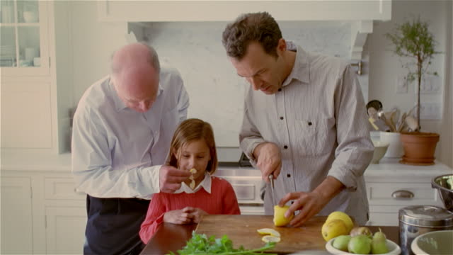 ms, man cutting lemon in kitchen, daughter (8-9 years) and father watching - smelling stock videos and b-roll footage