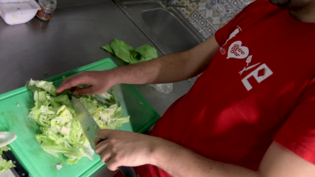 man cutting lettuce for salad on cutting board in commercial kitchen - chopped lettuce stock videos & royalty-free footage