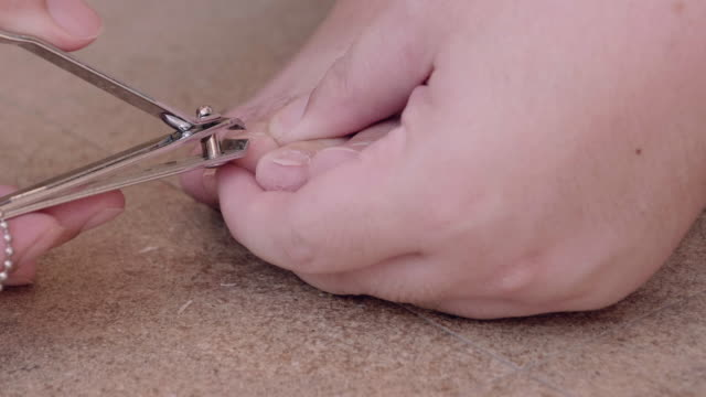 CU : Man cutting nails on feet with nail clippers