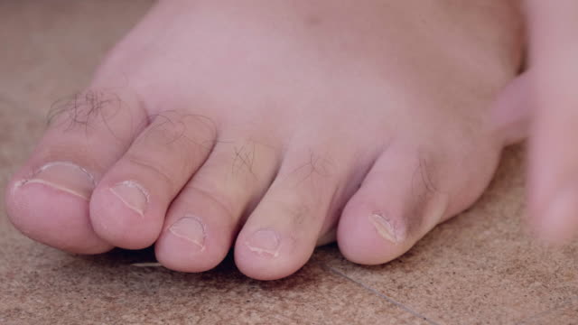 cu : man cutting nails on feet with nail clippers - human toe stock videos and b-roll footage
