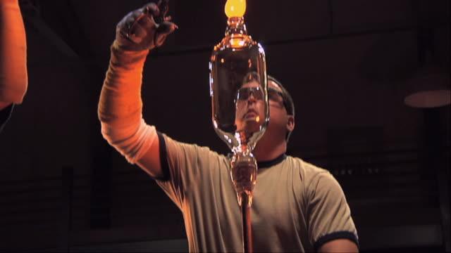 ms tu man cutting off molten glass bit on vase at a glass blowing factory / windsor, vermont, usa - glasbläser stock-videos und b-roll-filmmaterial