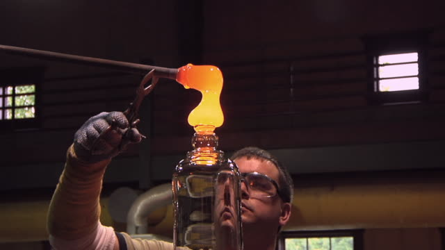 CU ZO WS Man cutting off molten glass bit on vase at glass blowing factory / Windsor, Vermont, USA