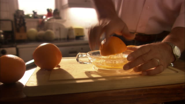 Man cutting oranges on wood cutting board and squeezing them into glass juicer to make orange juice