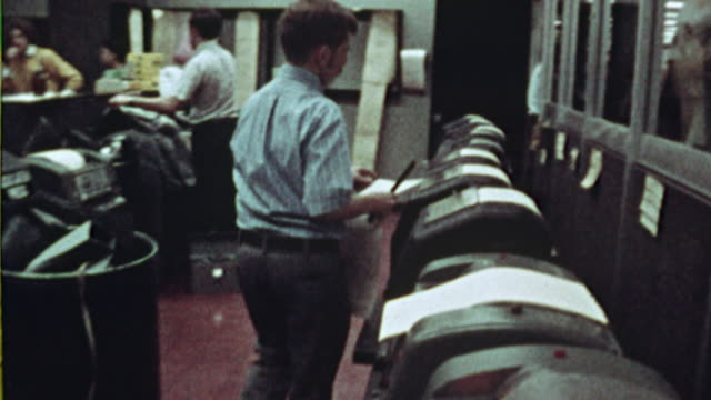 vídeos de stock e filmes b-roll de ms, man cutting papers from teleprinters in newsroom, 1970's, los angeles, california, usa - sala de imprensa