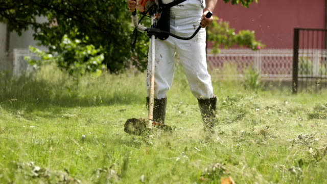 man cutting the grass with a lawnmower - mowing stock videos & royalty-free footage