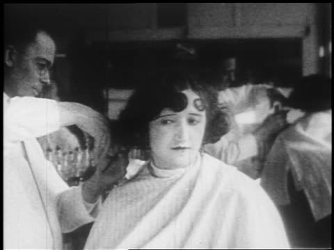 b/w 1925 man cutting woman's hair in barber shop / newsreel - 1925 stock videos & royalty-free footage