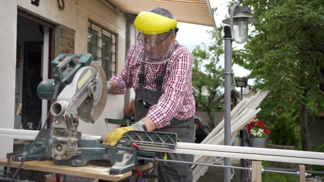 vídeos de stock, filmes e b-roll de homem cortando madeira em sua oficina de casa - serra circular