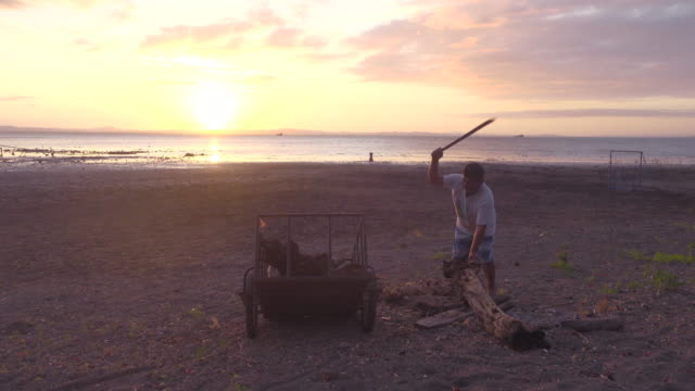 Man cutting wood with a big knife in front of a beach at sunset. Cocibolca lake at Ometepe Island, Nicaragua.