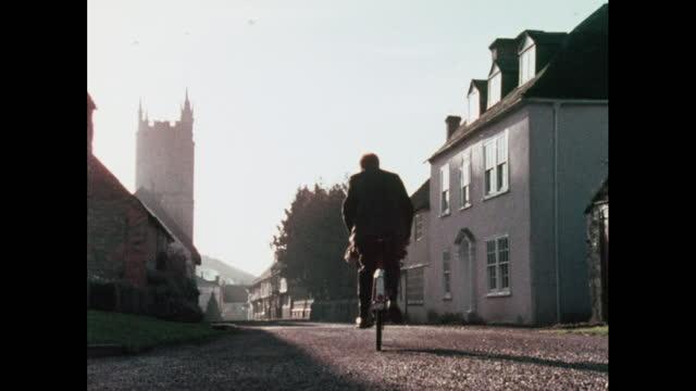 man cycles through village, uk, 1970s - village stock videos & royalty-free footage