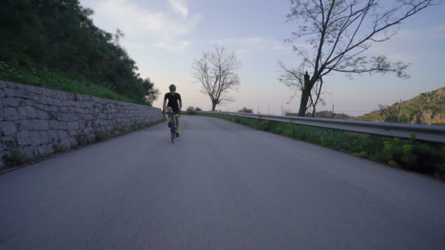 a man cycling on a bicycle, riding on road bikes in italy. - motorradfahrer stock-videos und b-roll-filmmaterial