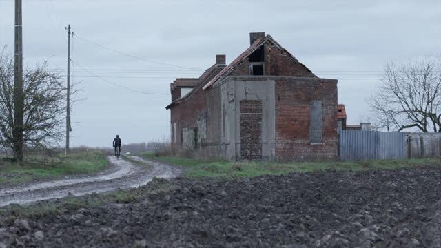 vidéos et rushes de man cycling on bicycle on parix-roubaix cobblestone roads riding past an abandoned building on road bikes in france. - a l'abandon