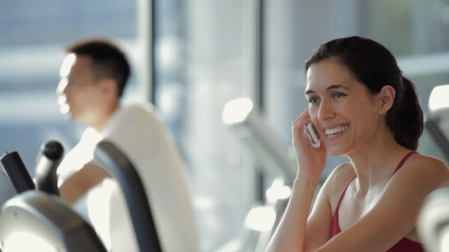 MS PAN Man cycling on exercise bike, woman talking on cell phone in gym / Vancouver, British Columbia, Canada