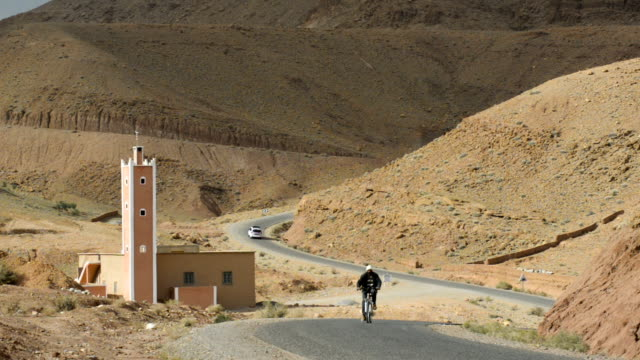 man cycling past mosque, valley of the roses, morocco, north africa - minaret stock videos & royalty-free footage