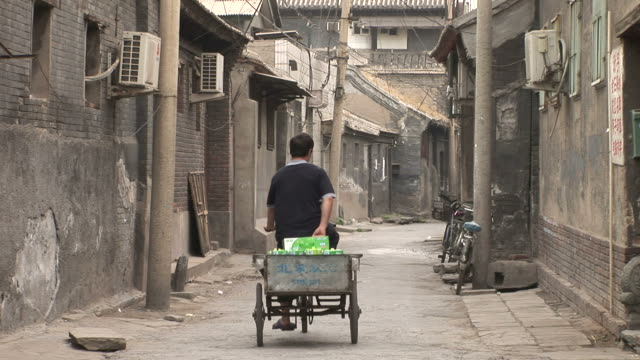 Man cycling through a narrow road in Old Beijing China