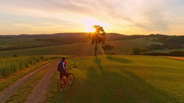 vídeos de stock, filmes e b-roll de aerial slo mo homem ciclismo de subida ao pôr do sol - colina acima