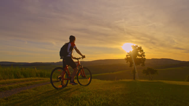 SLO MO Man cycling uphill at sunset