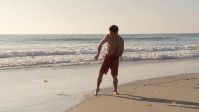 man dances at waters edge at the beach - サーフパンツ点の映像素材/bロール