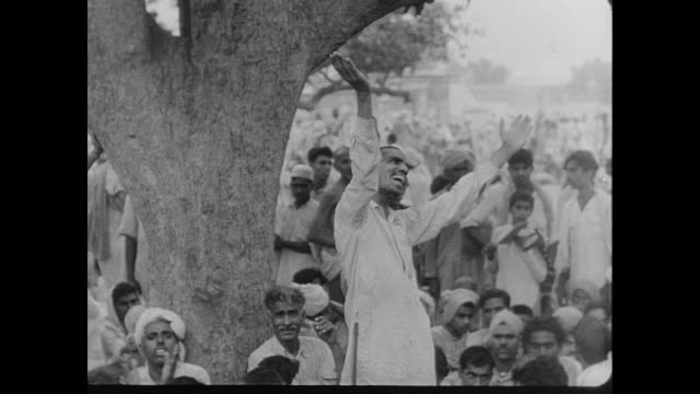 A man dances happily under a tree surrounded by a crowd of men and boys