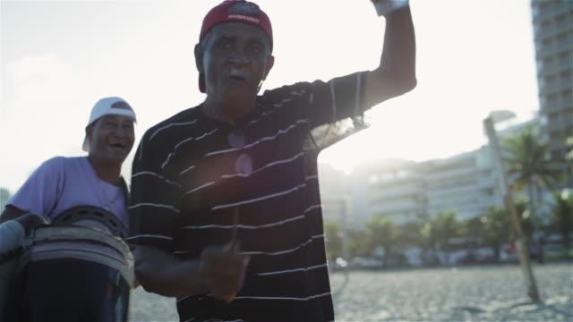vidéos et rushes de ms a man dances while others play instruments on ipanema beach / rio de janeiro, brazil - musicien