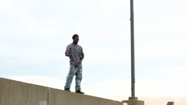 MS LA Man dancing along rooftop wall