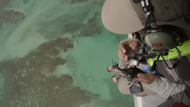 Man dangles out of helicopter over shallow tropical sea, UAE