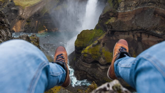 man dangling with his feet, sitting on edge of a canyon - hanging stock videos & royalty-free footage