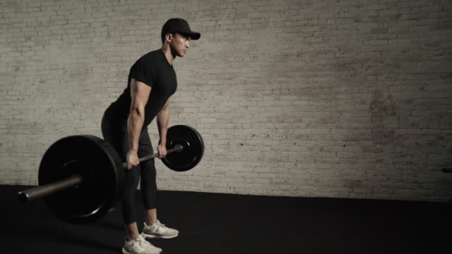 Man deadlifts with barbell