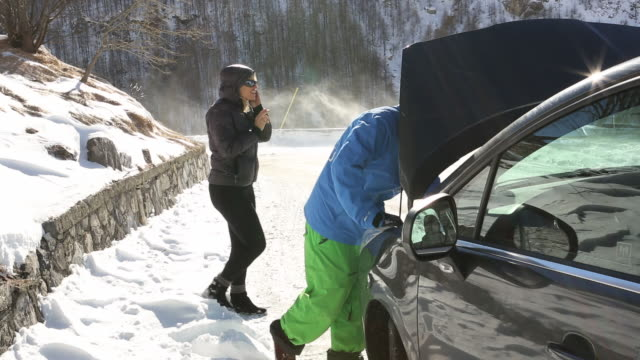 vidéos et rushes de man deals with car breakdown on snowy road, woman talks on phone - panne de voiture