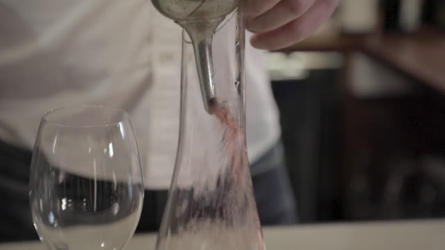 a man decants red wine into a decanter - decanter stock videos & royalty-free footage
