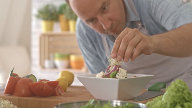 Man decorating vegetable salad with sprouts