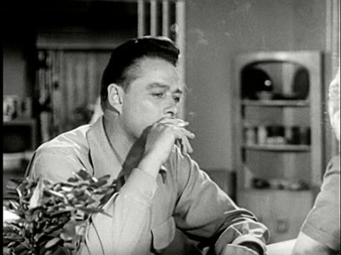 vídeos de stock, filmes e b-roll de 1952 cu man deep in thought / zo to ms man taking drag of cigarette / man across counter talking to him / back of woman standing beside talking man listening / man nods while exhaling giving man his attention/ audio - terno