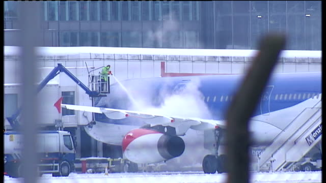 ext man deicing wings of aircraft with spray hose snowplough along runway area past parked aircraft ground staff vehicle along through snow - snow vehicle stock videos and b-roll footage