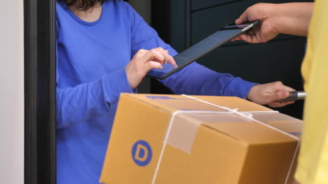 Man delivering a package and asking for a signature on Digital tablet, Close upMan delivering a package and asking for a signature on Digital tablet, Close up